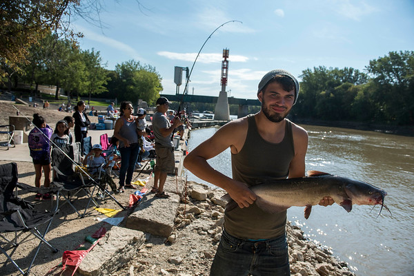 DAVID LIPNOWSKI / WINNIPEG FREE PRESS  Joseph Patterson holds a 77cm Catfish he and his father caught as hundreds of people registered to be part of a shoreline fall fishing derby along the Assiniboine River at the Forks in support of Marymound School and the Never Alone Foundation Saturday September 3, 2016.