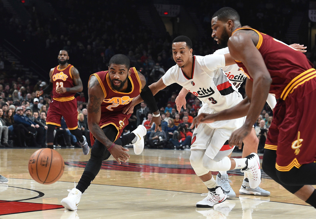 . Cleveland Cavaliers guard Kyrie Irving goes after a loose ball with Portland Trail Blazers guard C.J. McCollum during the first half of an NBA basketball game in Portland, Ore., Wednesday, Jan. 11, 2017. (AP Photo/Steve Dykes)