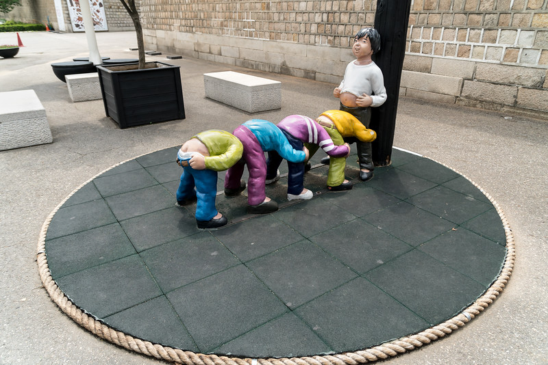 """Apparently this game is called """"Puck"""". But I don't get it. This statue is standing outside the Gyeongbokgung Palace. Of course."""