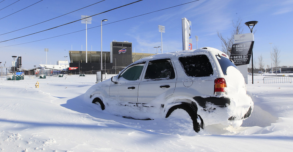 . An abandoned car sits in front of a snow covered Ralph Wilson Stadium home of the Buffalo Bills in Orchard Park, N.Y. on Wednesday, Nov. 19, 2014.  A ferocious lake-effect storm left the Buffalo area buried under 6 feet of snow Wednesday, trapping people on highways and in homes, and another storm expected to drop 2 to 3 feet more was on its way. (AP Photo/The Buffalo News, Harry Scull Jr.)