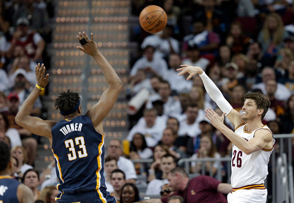 . Cleveland Cavaliers\' Kyle Korver, right, passes over Indiana Pacers\' Myles Turner in the second half in Game 1 of a first-round NBA basketball playoff series, Saturday, April 15, 2017, in Cleveland. (AP Photo/Tony Dejak)