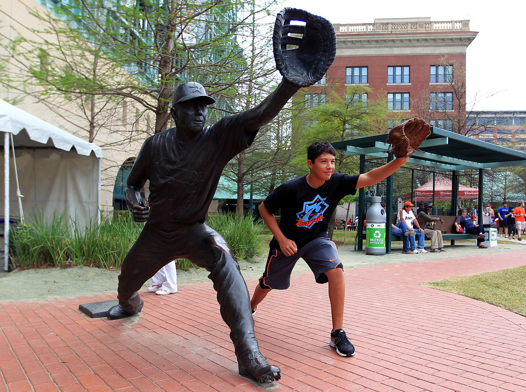 . Angel Davila poses for a photo next to a Jeff Bagwell statue during the street festival outside of Minute Maid Park,before an opening day baseball game between the Houston Astros and the Texas Rangers, Sunday, March 31, 2013, in Houston. (AP Photo/Houston Chronicle,  Karen Warren)