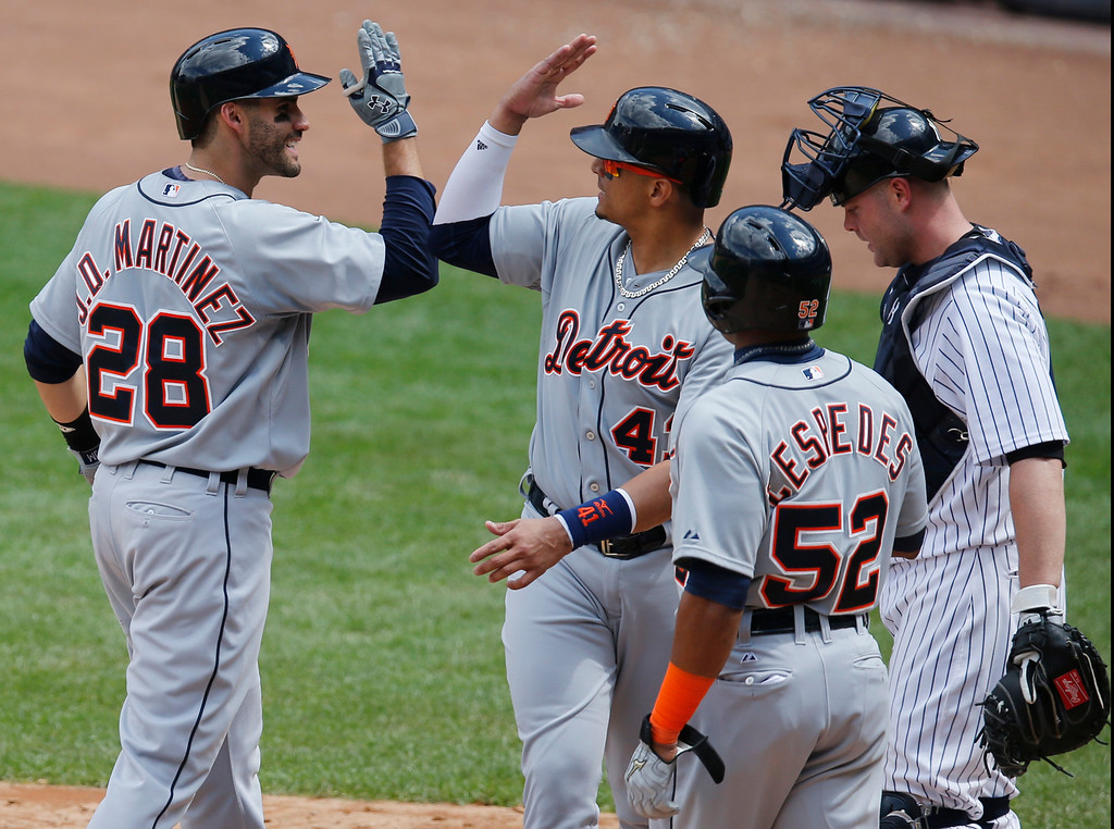 . Detroit Tigers J.D. Martinez (28) greets Victor Martinez, and Yoenis Cespedes after hitting a sixth-inning, three-run home run   in a baseball game against the New York Yankees at Yankee Stadium in New York, Sunday, June 21, 2015. Yankees catcher Brian McCann looks down, far right.  (AP Photo/Kathy Willens)