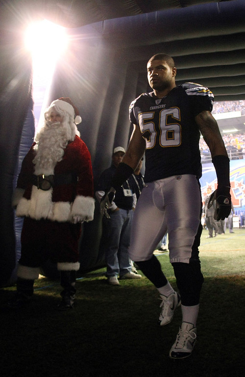 . Shawne Merriman #56 of the San Diego Chargers enters the game with Santa Claus looking on during the first half of their NFL game against the Denver Broncos at Qualcomm Stadium December 24, 2007 in San Diego, California.  (Photo by Donald Miralle/Getty Images)