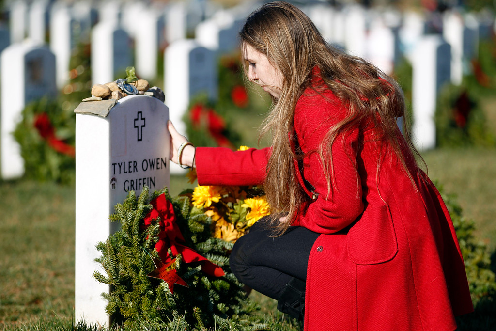 . Bronwen Desena prays over the grave of her friend, Marine Lance Cpl. Tyler Owen Griffin, of Voluntown, Ct., after she placed a holiday wreath at his grave in Section 60 at Arlington National Cemetery in Arlington, Va., Saturday Dec. 15, 2012, during Wreaths Across America Day. Wreaths Across America was started in 1992 at Arlington National Cemetery by Maine businessman Morrill Worcester and has expanded to hundreds of veterans\' cemeteries and other locations in all 50 states and beyond. (AP Photo/Jose Luis Magana)