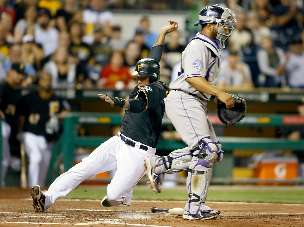 . Pittsburgh Pirates\' Jose Tabata, left, scores from third behind Colorado Rockies catcher Wilin Rosario on a bunt by Josh Harrison in the sixth inning of a baseball game on Saturday, Aug. 3, 2013, in Pittsburgh. (AP Photo/Keith Srakocic)