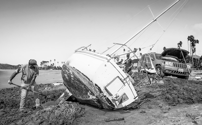 Retired firefighter Chris Benton digs out a storm beached sailboat as Josh Luft, a Marine Electrician prepares to pump the boat dry.