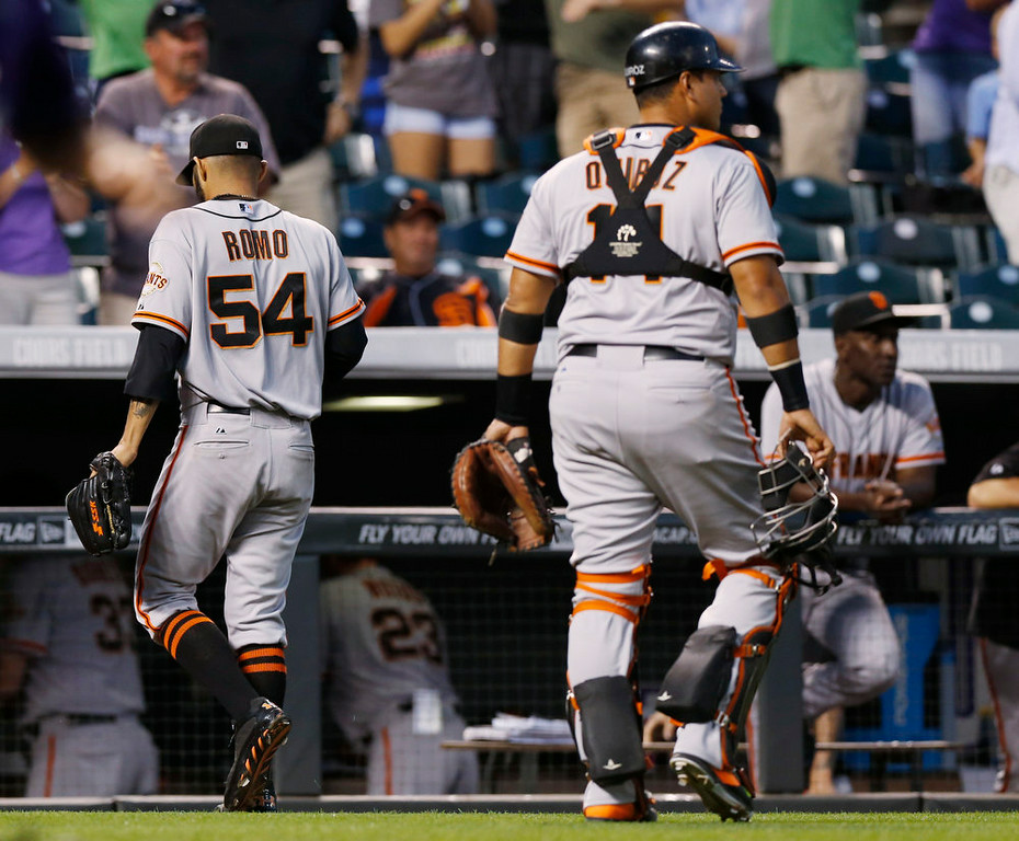 . the San Francisco Giants relief pitcher Sergio Romo, left, walks off the diamond with catcher Guillermo Quiroz after Romo gave up a walkoff, RBI-single to Colorado Rockies\' Charlie Blackmon in the ninth inning of the Rockies\' 10-9 victory in a baseball game in Denver on Monday, Sept. 1, 2014. (AP Photo/David Zalubowski)