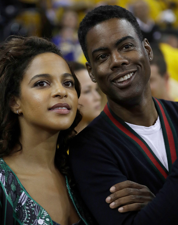 . Comedian Chris Rock, right, smiles next to Megalyn Echikunwoke before Game 5 of basketball\'s NBA Finals between the Golden State Warriors and the Cleveland Cavaliers in Oakland, Calif., Monday, June 12, 2017. (AP Photo/Marcio Jose Sanchez)