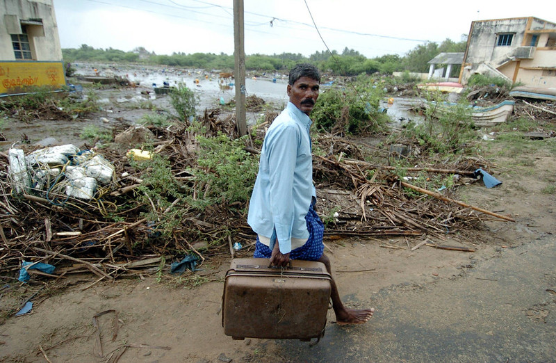 . A man carries his suitcase as he leaves the devastated Karmavadi village in the Nagapattinam district, some 350 km south of Madras on December 27, 2004, after tidal waves hit the region. The death toll in southern India from tidal waves that battered much of Asia crossed 6,800 Monday with thousands still missing, officials said. The official count of 6,823 dead included some 3,000 in the Andaman and Nicobar Islands, close to the epicenter of the Indonesian earthquake that caused the tsunamis, and another 3,600 in the southern Indian state of Tamil Nadu and the former French colony of Pondicherry.    PRAKASH SINGH/AFP/Getty Images