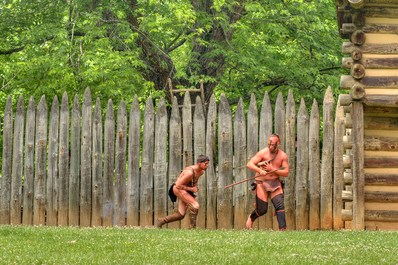 Native American reenactors plant a smoke bomb just outside the walls of the fort during the Siege of Fort Watauga at Sycamore Shoals State Park in Elizabethton, VA on Saturday, May 17, 2014. Copyright 2014 Jason Barnette  The Siege of Fort Watauga is a two-day reenactment held each year at the recreation of the fort inside Sycamore Shoals State Historic Park. The reenactment brings in dozens of reenactors and hundreds of visitors as they tell the story of an attack on the early settlers village by Dragging Canoe, and how they successfully defended themselves. During the reenactment, the fort is open to the public with demonstrations of all areas of early settler life on the frontiers.