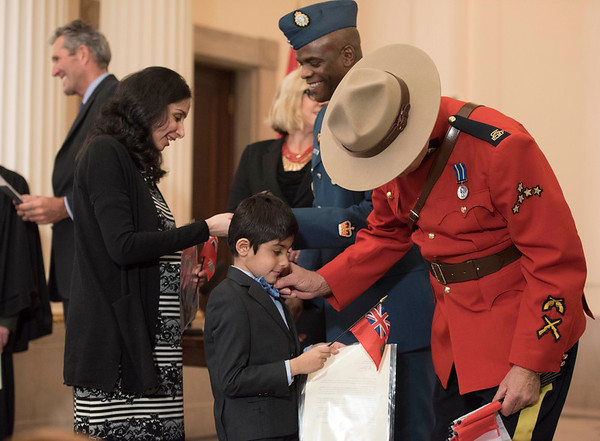 Divya Pahwa and her son Parth receive Canadian flags, and Parth gets his bowtie adjusted by a mountie during a citizenship ceremony after the family became Canadian Citizens at the Manitoba Legislative Building Wednesday February 1, 2017. His family are originally from India. (David Lipnowski for Metro News)