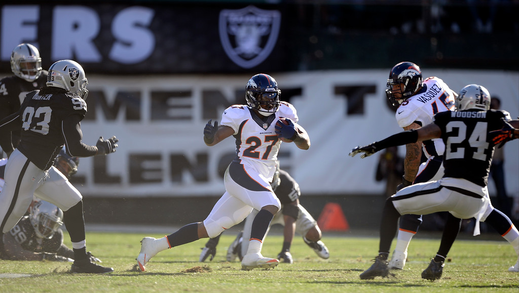 . Denver Broncos running back Knowshon Moreno (27) picks up a big gain as Oakland Raiders free safety Charles Woodson (24) moves in during the first quarter at O.co Coliseum. (Photo by John Leyba/The Denver Post)