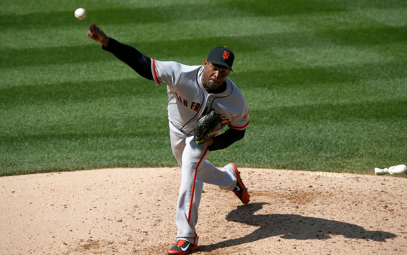 . San Francisco Giants relief pitcher Santiago Casilla works against the Colorado Rockies in the ninth inning of the Giants\' 4-2 victory in a baseball game in Denver on Monday, Sept. 1, 2014. The game was resumed in the bottom of the sixth inning of play when it was suspended because of rain on May 22. (AP Photo/David Zalubowski)