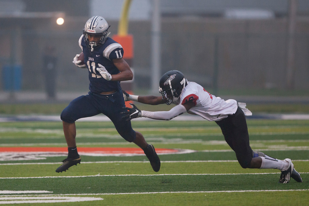 . Jen Forbus - The Morning Journal<br> Lorain running back Daylin Dower tries to evade St. Joseph\'s William Kalonjl on Sept. 14.