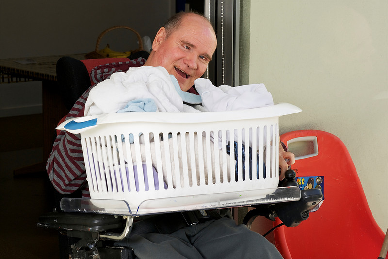 Man with a disability holding a clothes basket,