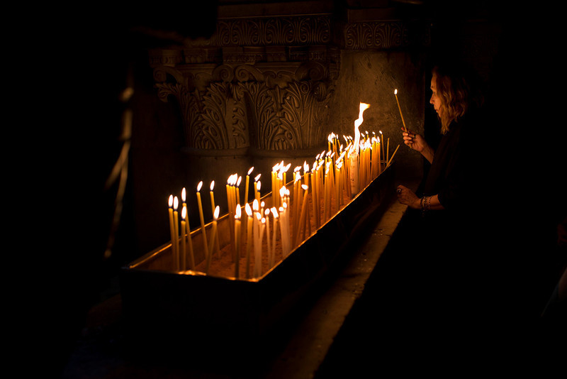 . A Christian Catholic pilgrim lights a candle inside the Church of the Holy Sepulcher, traditionally believed to be the site of the crucifixion of Christ, in Jerusalem\'s Old City, Friday, March 29, 2013. Less than 2 percent of the population of Israel and the Palestinian territories is Christian, mostly split between Catholicism and Orthodox streams of Christianity. Christians in the West Bank wanting to attend services in Jerusalem must obtain permission from Israeli authorities. Israel\'s Tourism Ministry said it expects some 150,000 visitors in Israel during Easter week and the Jewish festival of Passover, which coincide this year. (AP Photo/Bernat Armangue)