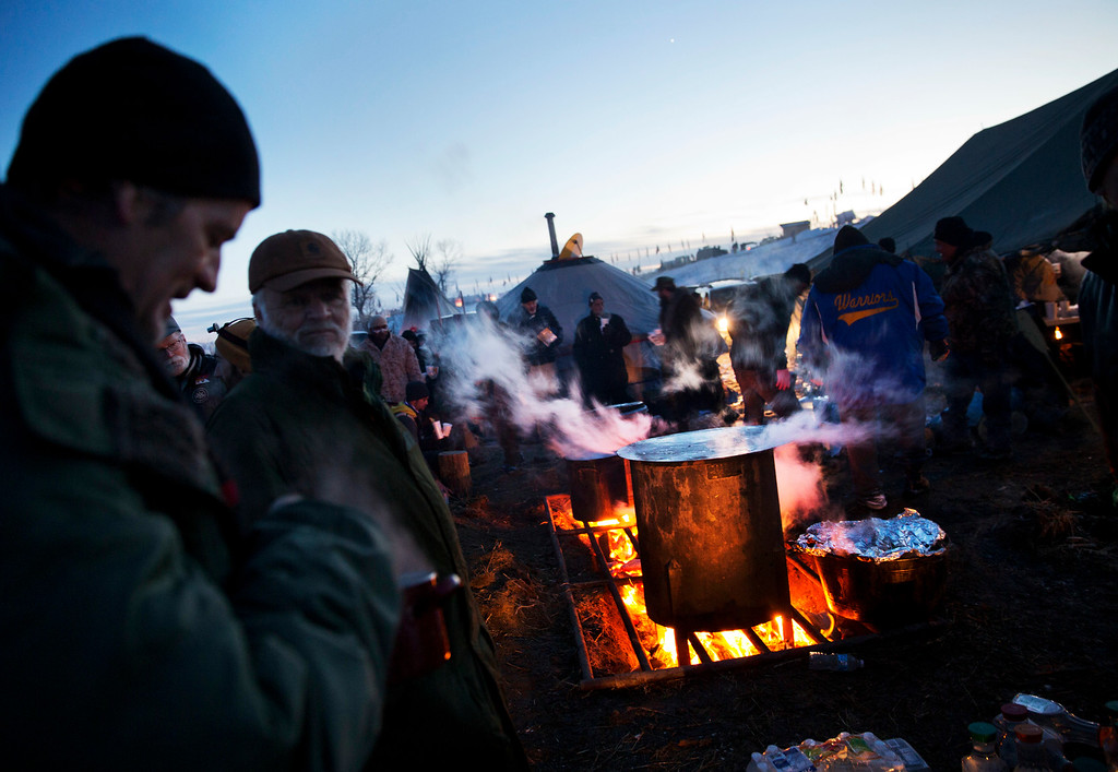 . Veterans line up for dinner at the Oceti Sakowin camp where people have gathered to protest the Dakota Access oil pipeline in Cannon Ball, N.D., Sunday, Dec. 4, 2016. The U.S. Army Corps of Engineers said Sunday afternoon that the four-state, $3.8 billion Dakota Access oil pipeline cannot be built under Lake Oahe, a Missouri River reservoir where construction had been on hold.  (AP Photo/David Goldman)