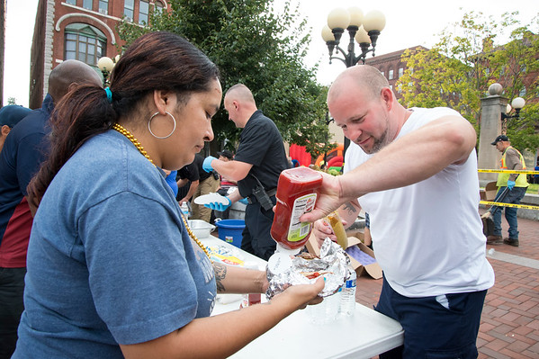 08/06/19 Wesley Bunnell | Staff The New Britain and CCSU Police held National Night out in Central Park on Tuesday evening as part of a nationwide night out designed to foster camaraderie between police and local communities. Alderman Francisco Santiago helps a Rosa Roldan with her hot dogs.