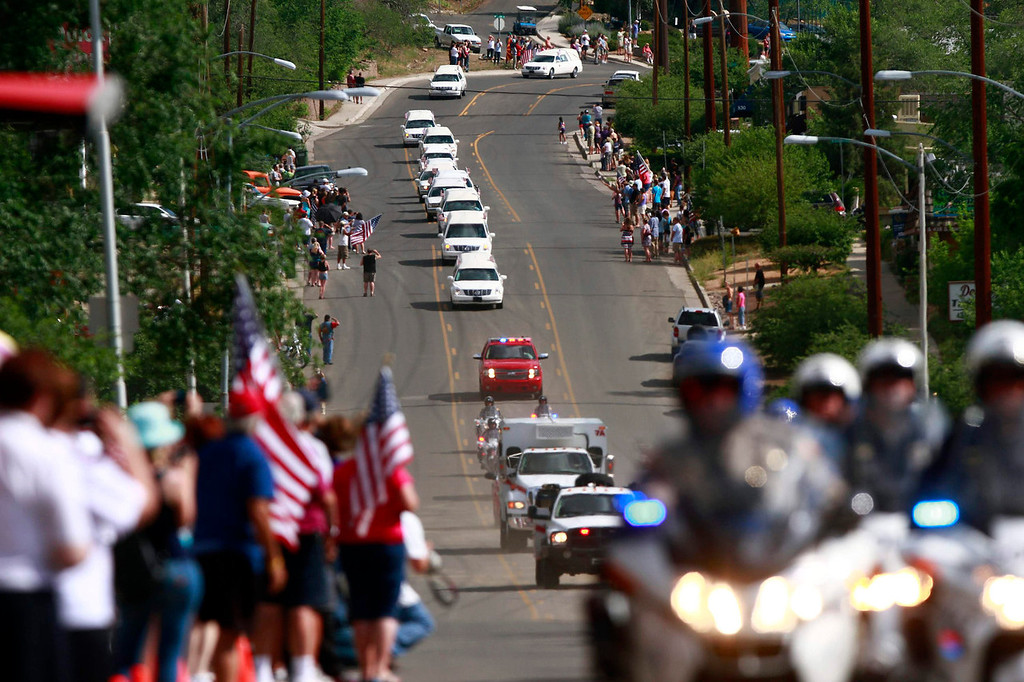 . Hearses carrying the remains of the 19 members of the Granite Mountain Hotshots firefighting team, who were killed fighting the Yarnell Fire, move in a motorcade from the Maricopa County Medical Examiner\'s office in Phoenix, Arizona July 7, 2013. A solemn procession of 19 white hearses carrying the remains of firefighters killed battling an Arizona wildfire left Phoenix accompanied by police motorcycle outriders on Sunday on a final journey passing through the crew\'s hometown. REUTERS/Joshua Lott