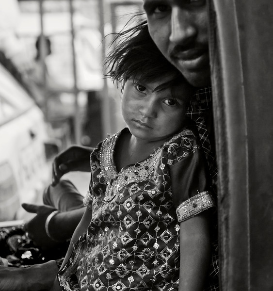 Girl riding on an auto rickshaw with her father.   Old Delhi, India, 2011.