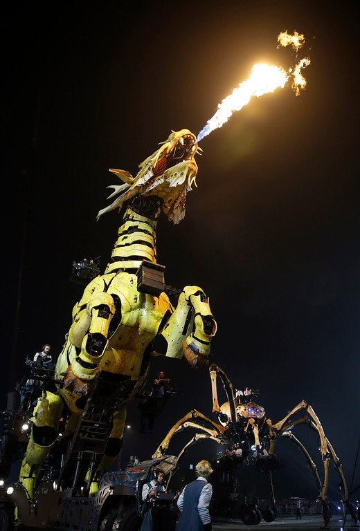 """. French production company La Machine\'s latest creation \""""the Long Ma\"""" or Dragon Horse spews fire next to the mechanical spider also known as La Princesse during a performance in front of the Bird\'s Nest Stadium in Beijing, China Sunday, Oct. 19, 2014. The performance, which attended by French Foreign Minister Laurent Fabius and his Chinese counterpart Wang Yi, marked the climax of celebrations for the 50th anniversary of Sino-French diplomatic relations. (AP Photo/Andy Wong)"""