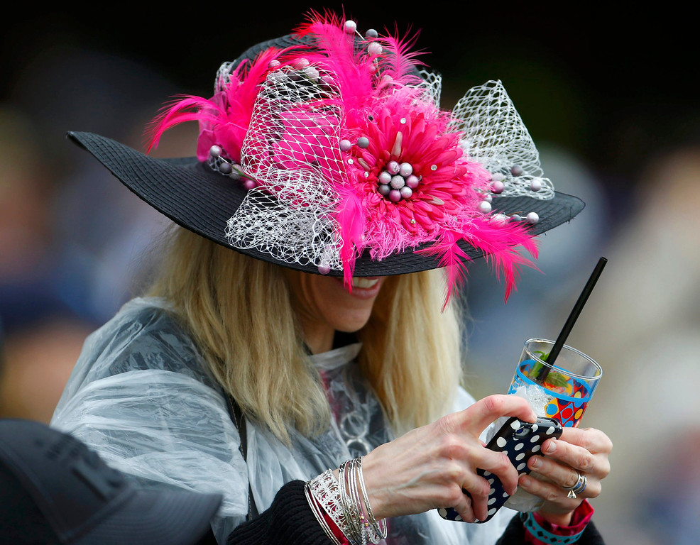 . A spectator uses her mobile phone while wearing her fancy hat prior to the running of the 139th Kentucky Derby horse race at Churchill Downs in Louisville, Kentucky, May 4, 2013. REUTERS/Jeff Haynes