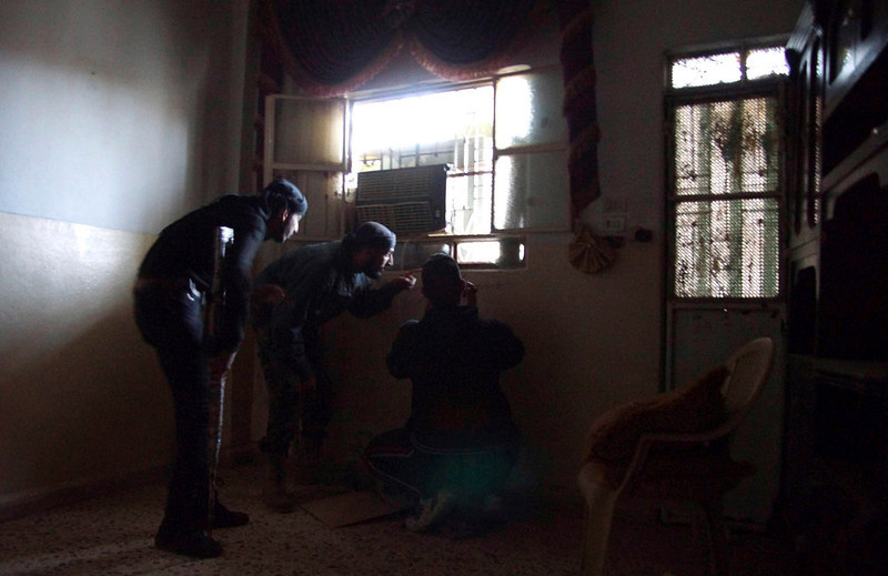 . A Free Syrian Army fighter (C) gestures, as his colleague (R) holds his camera inside a house in Deir al-Zor April 16, 2013. Picture taken April 16, 2013. REUTERS/ Khalil Ashawi