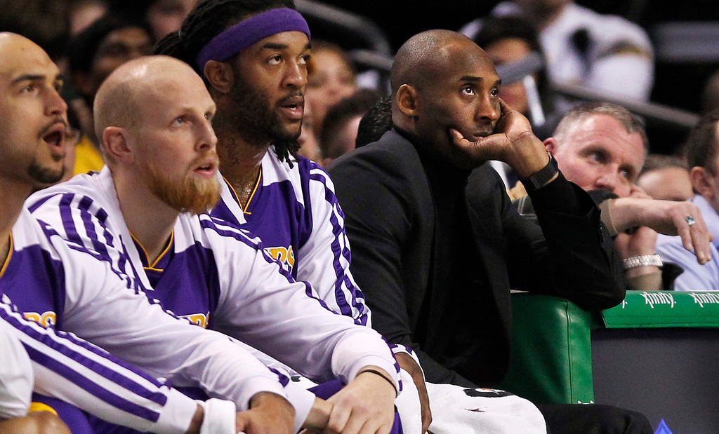 . Los Angeles Lakers guard Kobe Bryant, fourth from left, sits on the bench as he watches teammates play against the Boston Celtics during the first quarter of an NBA basketball game, in Boston, Friday, Jan. 17, 2014. Bryant has been sidelined after fracturing his left knee in December. (AP Photo/Charles Krupa)