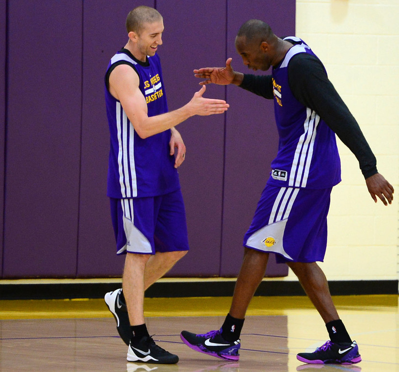 . Lakers\' Kobe Bryant and Steve Blake celebrate a basket as they participate in team practice at the Toyota Sports Center Tuesday, November 19, 2013, in El Segundo, CA.  After practice, Bryant discusses with the media his return from injury.