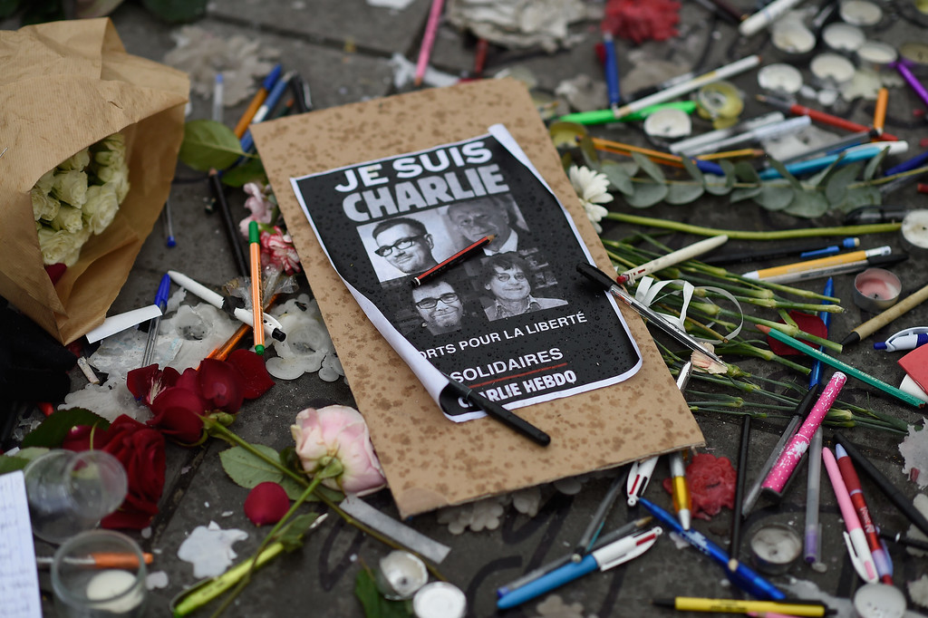 . People lay flowers and candles at the Place de la Republique at midday in solidarity with victims of yesterday\'s terrorist attack on January 8, 2015 in Paris, France.  Twelve people were killed including two police officers as two gunmen opened fire at the offices of the French satirical publication Charlie Hebdo on January 7.  (Photo by Pascal Le Segretain/Getty Images)