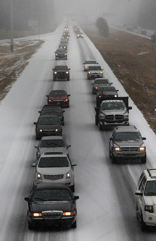 . Vehicles moves slowly on Interstate 575 in North West Ga., Tuesday, Jan. 28, 2014, near Kennesaw, Ga. Georgians stocked up on ice-melting chemicals, school systems closed, and road crews prepared to clear snow and ice from highways as a winter storm took aim. (AP Photo/Mike Stewart)