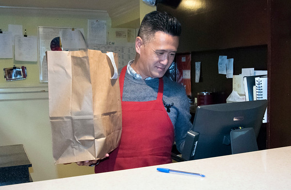 03/27/20 Wesley Bunnell | StaffrrFrank Kwok , co owner of Great Taste Restaurant, holds a to go bag as he rings out a customer at his restaurant on Monday afternoon. Governor Ned Lamont ordered all restaurants closed effective at 8 p.m. with the exception of take out and delivery.
