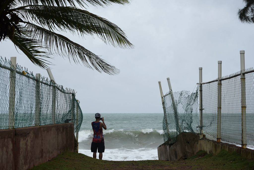 . A man photographs the ocean before the arrival of Hurricane Irma, in luquillo, Puerto Rico, Wednesday, Sept. 6, 2017. Irma roared into the Caribbean with record force early Wednesday, its 185-mph winds shaking homes and flooding buildings on a chain of small islands along a path toward Puerto Rico, Cuba and Hispaniola and a possible direct hit on densely populated South Florida. (AP Photo/Carlos Giusti)