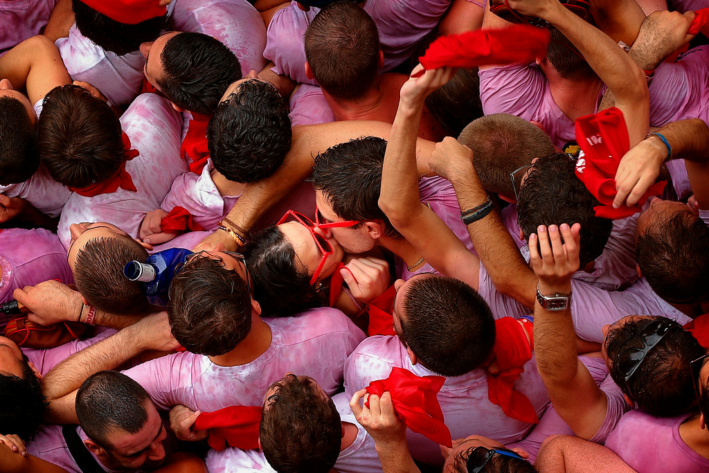 """. A couple of revelers kiss during the launch of the \'Chupinazo\' rocket, to celebrate the official opening of the 2014 San Fermin fiestas, in Pamplona, Spain, Sunday, July 6, 2014. Revelers from around the world kick off the festival with a messy party in the Pamplona town square, one day before the first of eight days of the running of the bulls glorified by Ernest Hemingway\'s 1926 novel \""""The Sun Also Rises.\"""" (AP Photo/Daniel Ochoa de Olza)"""