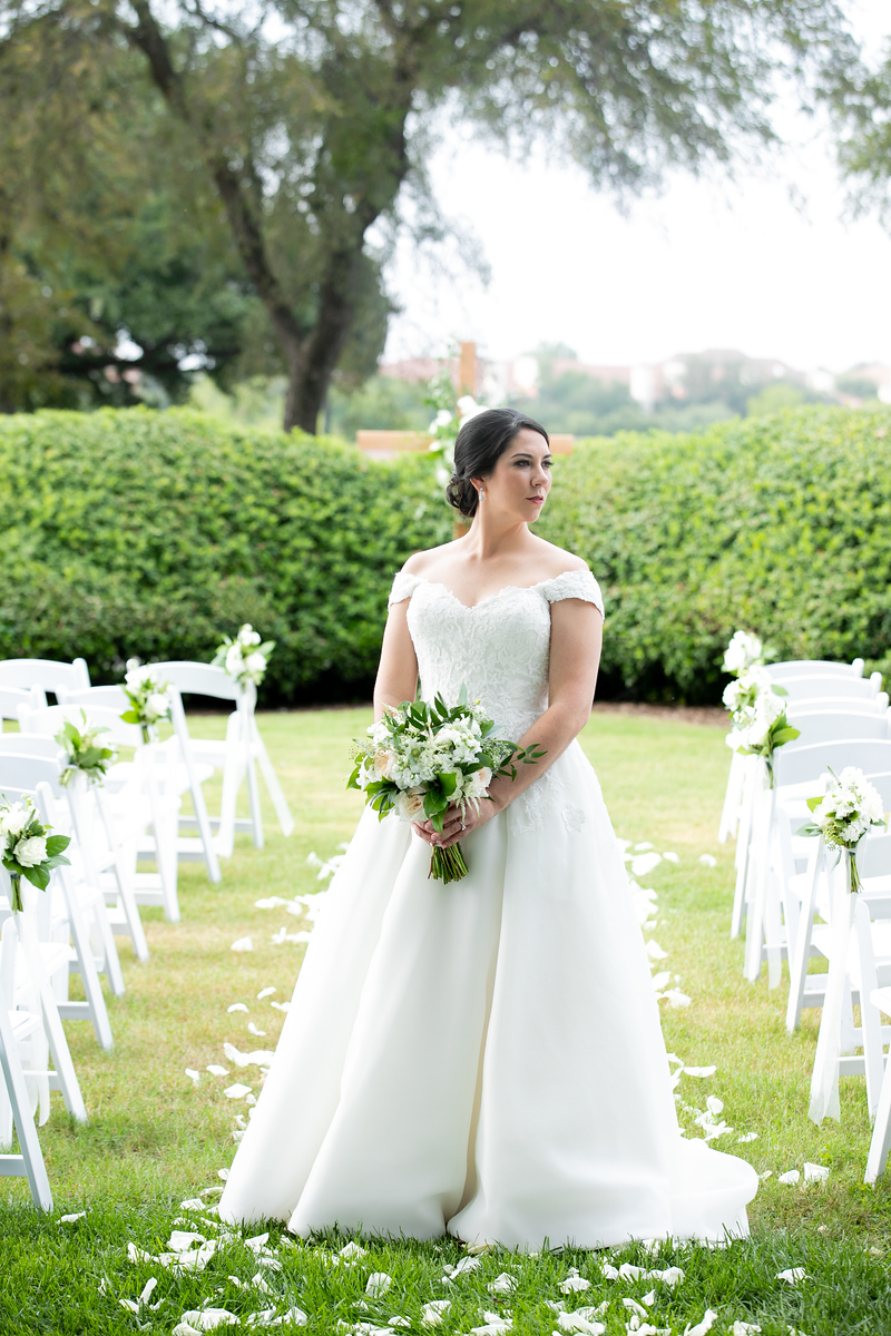 bride standing in the aisle holding her white and green wedding bouquet