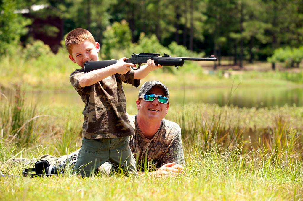 . Jeremy Chavez helps his son Ryan, 6, with target practice before a wild hog hunt at Great Southern Outdoors Wildlife Plantation in Union Springs, Alabama, Saturday June 16, 2012. Fast, smart and dangerous, the wild boar was once the most prized hunter\'s catch in ancient Greece. Now it is becoming a popular target of hunters in the United States. An explosion of wild pig populations has become such a nuisance that hunting seasons are being flung wide open for wild hog across the nation. REUTERS/Michael Spooneybarger