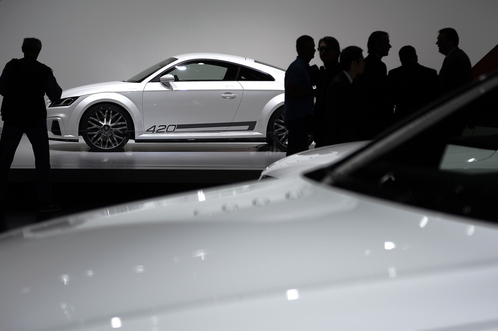 Description of . Visitors are seen in silhouette at the stand of  German carmaker  Audi during the press day of the Geneva Motor Show in Geneva, on March 5, 2014. (FABRICE COFFRINI/AFP/Getty Images)