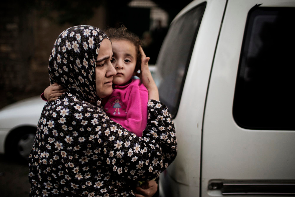 . A Palestinian woman protects her child while leaving a building damaged after an Israeli air raid in Gaza City November 19, 2012.   Israeli air strikes on Sunday killed 31 Palestinians in the bloodiest day so far of its air campaign on the Gaza Strip, as diplomatic efforts to broker a truce intensified.   MARCO LONGARI/AFP/Getty Images
