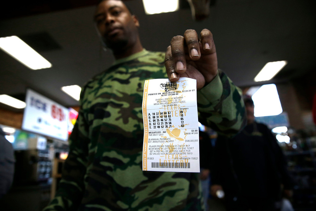 . John Hollis shows off his Mega Millions lottery ticket he purchased at the Fuel City convenience story Monday, Dec. 16, 2013, in Dallas. The Mega Millions jackpot soared to $586 million on Monday amid a frenzy of ticket purchases, a jump that pushed the prize closer to the $656 million U.S. record set last year. (AP Photo/LM Otero)