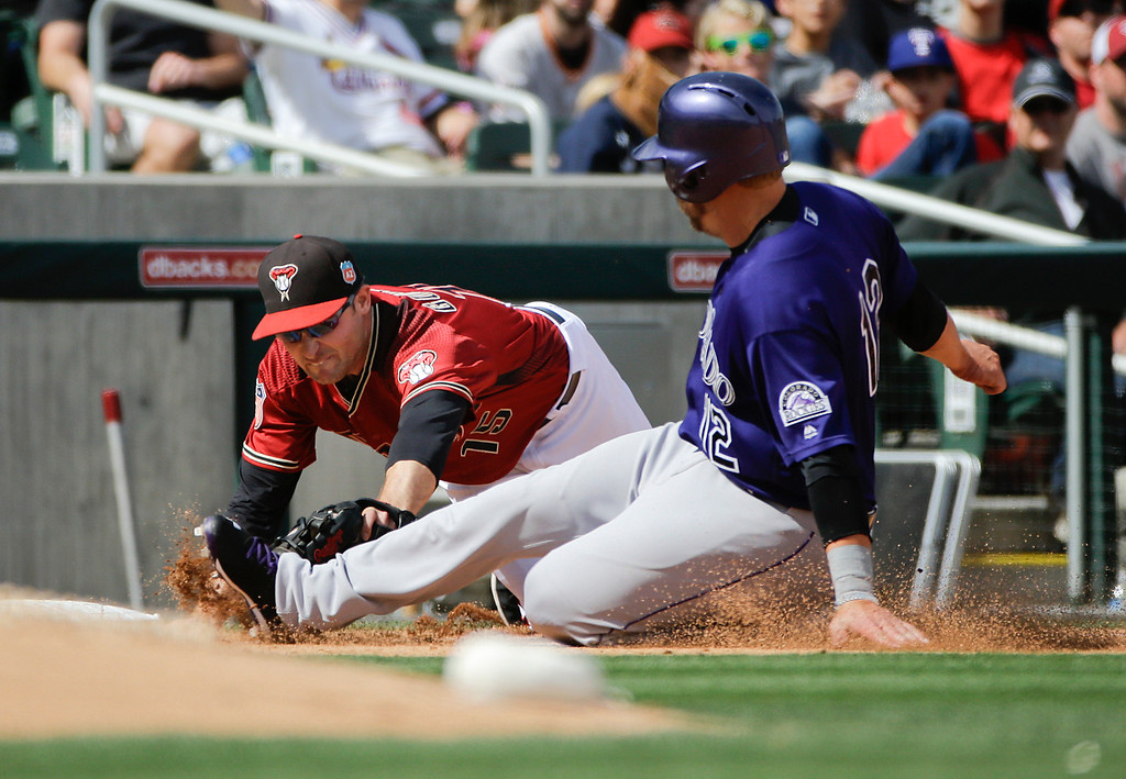 . Colorado Rockies\' Mark Reynolds, right, is tagged out by Arizona Diamondbacks third baseman Phil Gosselin during the fifth inning of a spring training baseball game Tuesday, March 29, 2016, in Scottsdale, Ariz. (AP Photo/Jae C. Hong)