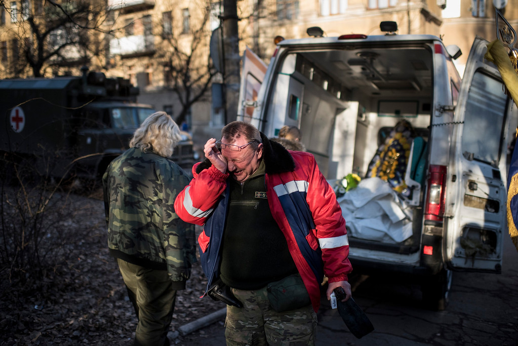 . A member of Ukrainian military medical unit cries for his four comrades killed near Debaltseve during a ceremony in Artemivsk, eastern Ukraine, Monday, Feb. 23, 2015.  Ukraine delayed a promised pullback of heavy weapons from the front line Monday in eastern Ukraine, blaming continuing attacks from separatist rebels.  (AP Photo/Evgeniy Maloletka)