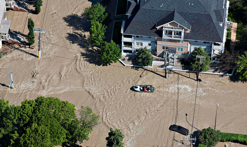 . A boat makes its way up a street after the Bow River overflowed its banks in a residential area of Calgary, Alberta June 22, 2013.  REUTERS/Andy Clark