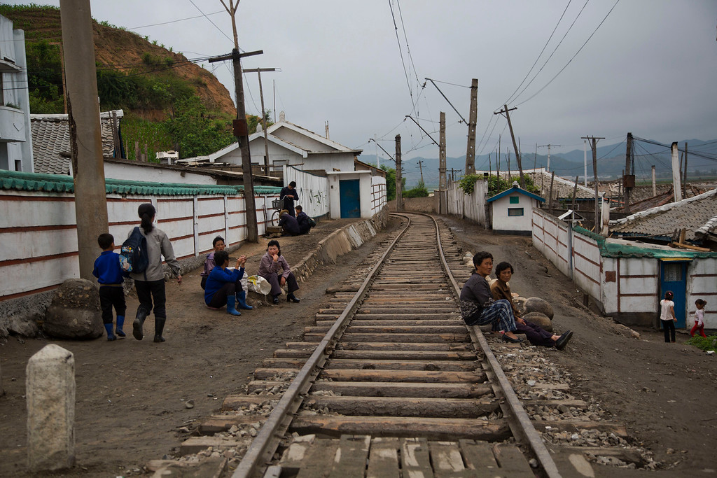 """. In this June 20, 2014 photo, North Korean people rest next to the railroad tracks in a town in North Korea\'s North Hamgyong province. The Associated Press was granted permission to embark on a weeklong road trip across North Korea to the countryís spiritual summit Mount Paektu. The trip was on North Korea\'s terms. An AP reporter and photographer couldn\'t interview ordinary people or wander off course, and government \""""minders\"""" accompanied them the entire way. (AP Photo/David Guttenfelder)"""