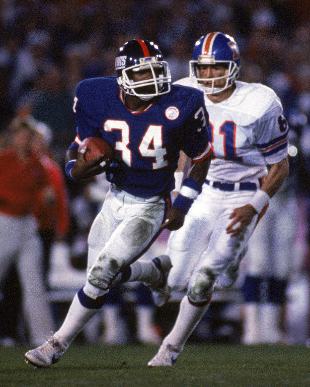 . Cornerback Elvis Patterson #34 of the New York Giants runs with the ball following an interception as wide receiver Steve Watson #81 of the Denver Broncos pursues during Super Bowl XXI at the Rose Bowl on January 25, 1987 in Pasadena, California.  (Photo by George Rose/Getty Images)