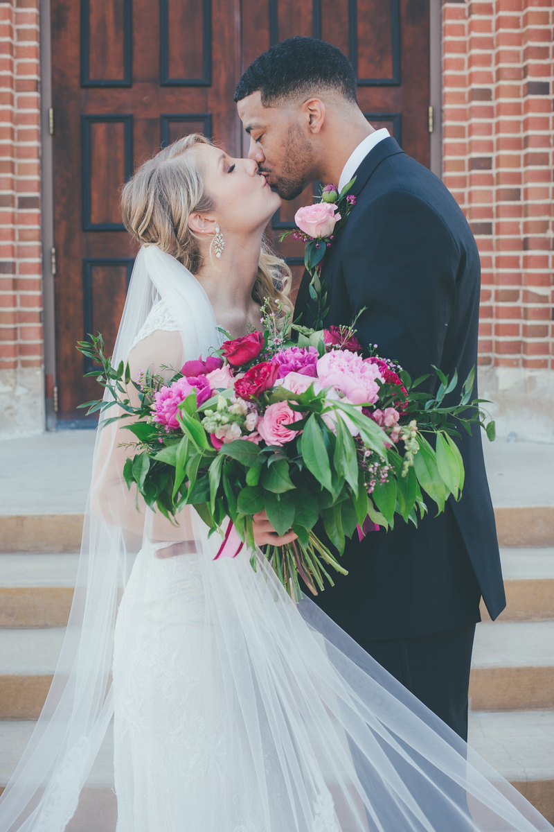 A bride and groom kissing in front of the church in which they are about to get married