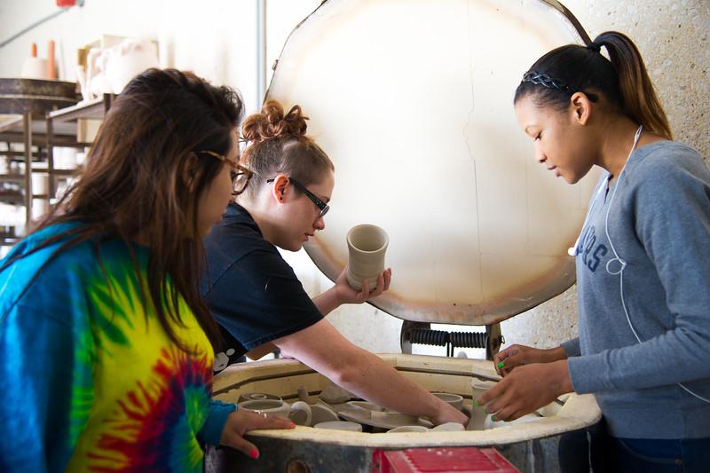 Students Jessica Facondo(left), Joanna Bolsins, and Brittni Carraway load a kiln full of ceramics to be fired.