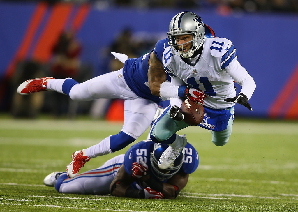 . Cole Beasley #11 of the Dallas Cowboys is tackled against  Terrell Thomas #24 and  Jon Beason #52 of the New York Giants during their game at MetLife Stadium on November 24, 2013 in East Rutherford, New Jersey.  (Photo by Al Bello/Getty Images)
