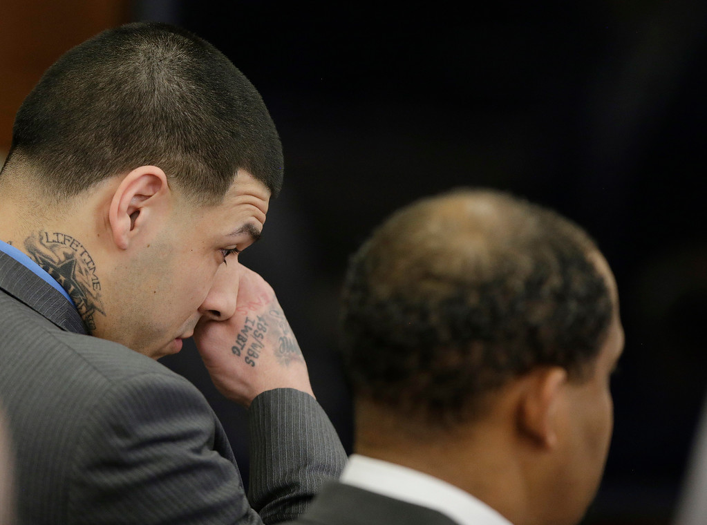 . Former New England Patriots tight end Aaron Hernandez wipes tears from his eyes as he stands with defense attorney Ronald Sullivan reacting to his double murder acquittal at Suffolk Superior Court Friday, April 14, 2017 in Boston. Hernandez stood trial for the July 2012 killings of Daniel de Abreu and Safiro Furtado who he encountered in a Boston nightclub. The former NFL player is already serving a life sentence in the 2013 killing of semi-professional football player Odin Lloyd. (AP Photo/Stephan Savoia, Pool)