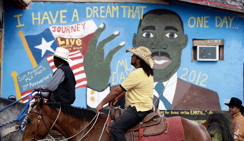 . Riders pass a mural as they take part in a march honoring Martin Luther King Jr., on Martin Luther King Day, Monday, Jan. 21, 2013, in San Antonio. The nation honors civil rights leader Martin Luther King Jr. on Monday, the same day as it celebrates the inauguration of the first black president to his second term. (AP Photo/Eric Gay)